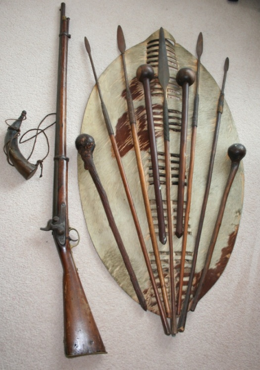 Zulu Weaponry, c1860-1879. A familiar sight hanging on the walls of many a regimental mess room, or traveller's hallway. The smaller war shield, or umbumbulozo, knobkerries, iklwa and percussion rifled musket and powder horn. IanKnkghtZulu.com